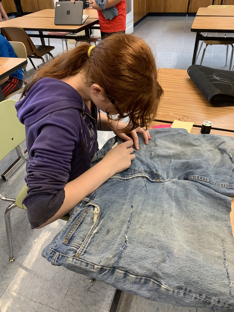 Amber practicing mending a pair of jeans!